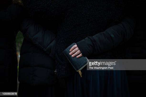 Yeshiva High School student holds a Siddur prayer book as she prays with her classmates at a memorial in front of the Tree of Life Synagogue on...