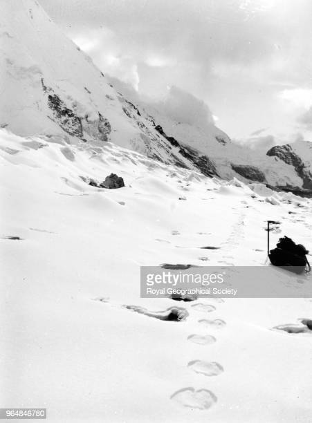 Yeti Footprint leading off into the mountains with rucksack and ice axe Nepal August 1951 Mount Everest Reconnaissance Expedition 1951