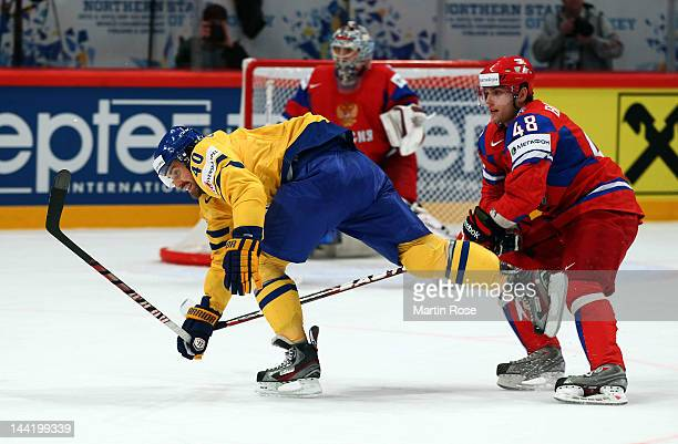 Yevgeni Biryukov of Russia and Henrik Zetterberg of Sweden battle for the puck during the IIHF World Championship group S match between Russia and...