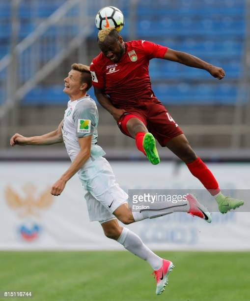 Yevgeni Chernov of FC Tosno and Sly of FC Ufa vie for the ball during the Russian Football League match between FC Tosno and FC Ufa at Petrovsky...