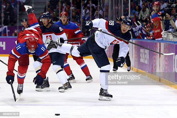 Yevgeni Malkin of Russia comes into contact with Richard Panik of Slovakia during the Men's Ice Hockey Preliminary Round Group A game on day nine of...