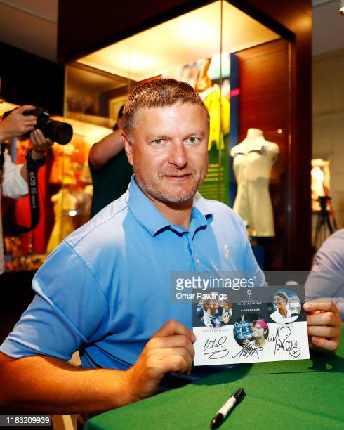 Yevgeny Kafelnikov pose for a picture holding a class of 2019 autographed card during a fan session in the museum at the Tennis Hall of Fame on July...
