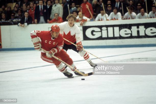 Yevgeny Mishakov of the Soviet Union skates with the puck as Bobby Clarke of Canada follows behind during the 1972 Summit Series at the Luzhniki Ice...
