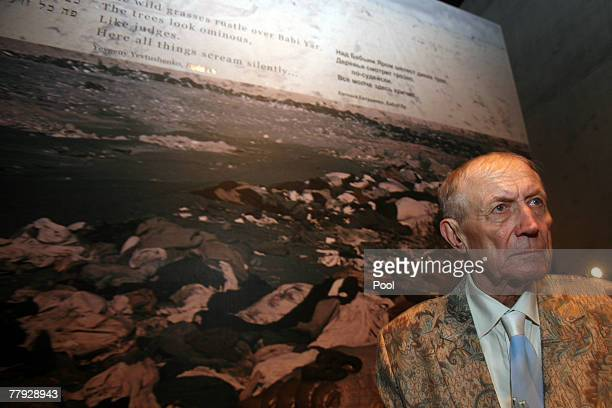 Yevgeny Yevtushenko a Russian poet novelist and literature professor stands next to his poem 'Babi Yar' written on a holocaust photo during his visit...