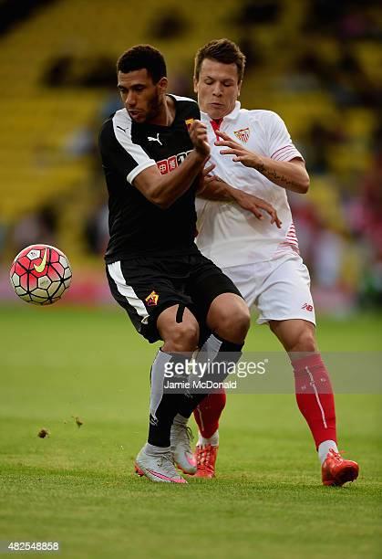 Yevhen Konoplyanka of Sevilla battles with Odion Ighalo of Watford during the pre season match beween Watford and Sevilla at Vicarage Road on July 31...