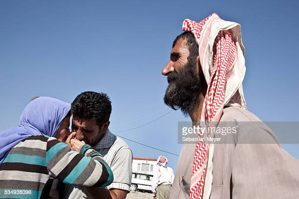 Yezidi man and woman embrace after crossing from Syria back into Iraq. Tens of thousands of Yezidi--an minority ethno-religious group in Iraq--have...