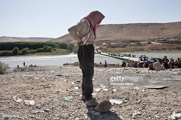 Yezidi man stands on the Iraqi bank of the Tigris after crossing from Syria back into Iraq. Tens of thousands of Yezidi--an minority ethno-religious...