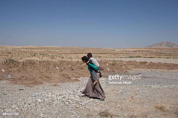 Yezidi woman carries her son on her back after crossing into Iraq from Syria. Tens of thousands of Yezidi--an minority ethno-religious group in...