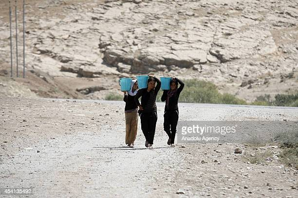 Yezidi women carry drinkable water with buckets in Zakho district a few kilometers from the IraqiTurkish border Dohuk on August 25 2014 Yezidis fled...