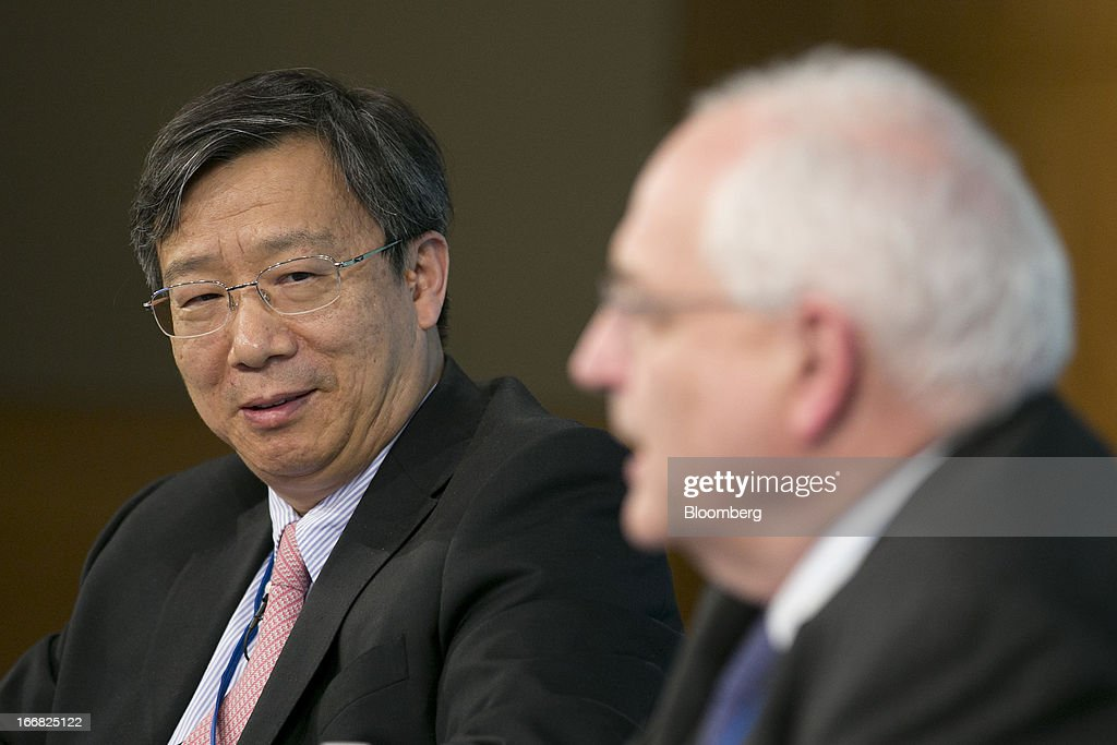 Yi Gang, deputy governor of the People's Bank of China, left, looks on as Martin Wolf, associate editor and chief economics commentator at the Financial Times, speaks at a macro policy discussion during the International Monetary Fund (IMF) and World Bank Group Spring Meetings in Washington, D.C., U.S., on Wednesday, April 17, 2013. As much as 20 percent of non-bank corporate debt in the weakest euro-area economies is unsustainable and may force companies to cut dividends and sell assets, dealing further blows to investor confidence, the IMF said. Photographer: Andrew Harrer/Bloomberg via Getty Images