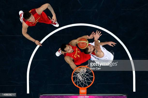 Yi Jianlian of China reaches for a rebound in the first half against Robert Archibald of Great Britain during the Men's Basketball Preliminary Round...