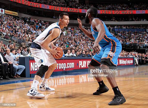 Yi Jianlian of the Dallas Mavericks looks to drive against James Harden of the Oklahoma City Thunder on February 1 2012 at the American Airlines...