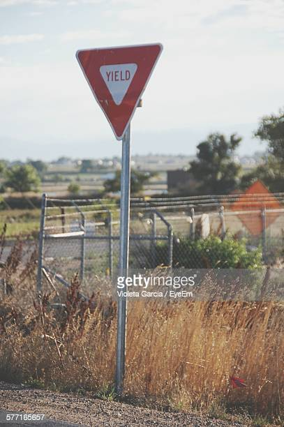 yield sign on roadside against sky - give way stock pictures, royalty-free photos & images