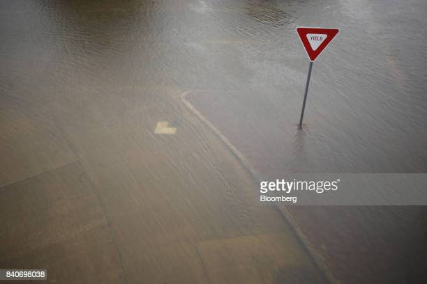 A yield sign stands IN floodwaters left behind by Hurricane Harvey in Dickinson Texas US on Tuesday Aug 29 2017 Estimates for damages caused by...