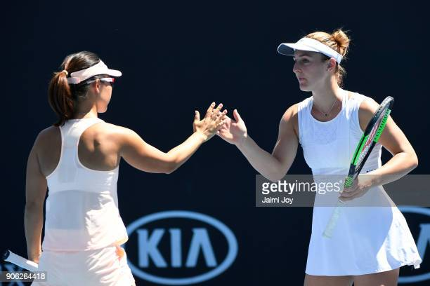 Yifan Xu of China and Gabriela Dabrowski of Canada talk tactics in their first round women's doubles match against Kirsten Flipkens of Belgium and...