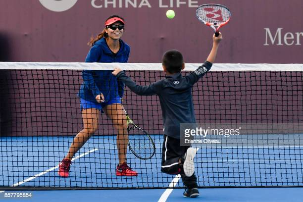 Yifan Xu of China, partner of Gabriela Dabrowski of Canada, plays tennis with a kid during the Inclub Clinic on day six of the 2017 China Open at the...