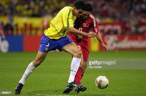 Yildiray Basturk of Turkey tackles Lucio of Brazil during the FIFA World Cup Finals 2002 SemiFinal match played at the Saitama Stadium in SaitamaKen...