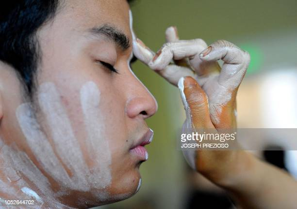 Yin Tom applies paint to Aqeel Hisham during the '3018 fashion show' at the 12th Annual Black New England Conference at the University of New...