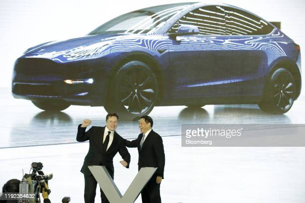 Ying Yong mayor of Shanghai right reacts to Elon Musk chief executive officer of Tesla Inc gesturing during the Tesla ChinaMade Model 3 Delivery...