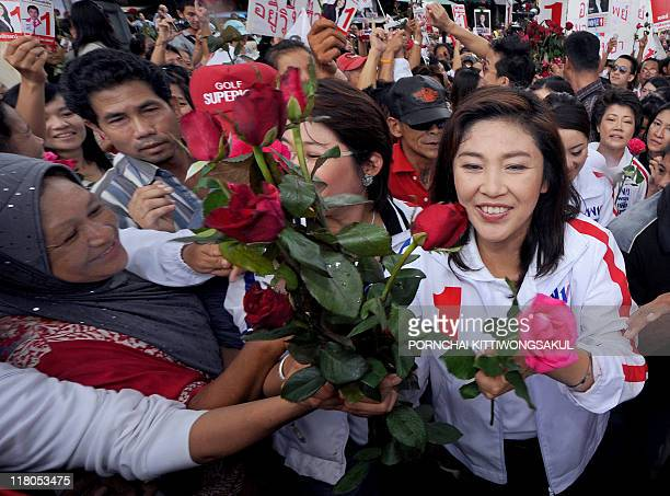 Yingluck Shinawatra sister of fugitive former Thai prime minister Thaksin Shinawatra and candidate for the Puea Thai Party receives roses from her...