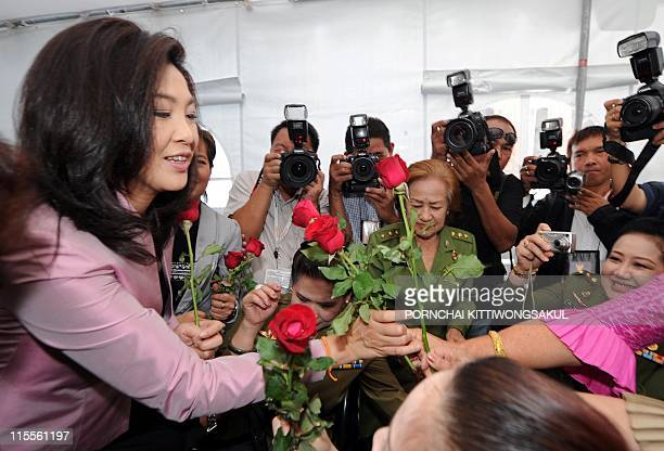 Yingluck Shinawatra sister of fugitive Thai exprime minister Thaksin Shinawatra receives roses during her election campaign in Bangkok on June 8 2011...