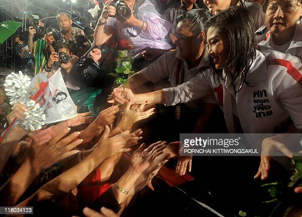 Yingluck Shinawatra sister of fugitive Thai exprime minister Thaksin Shinawatra receives roses from her supporters during an election campaign rally...
