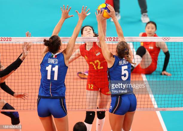 Yingying Li of Team China competes against Anna Danesi and Ofelia Malinov of Team Italy during the Women's Preliminary - Pool B volleyball on day...