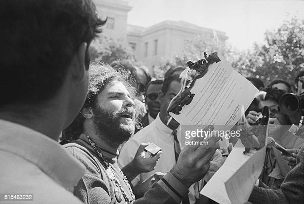 Yippie leader Jerry Rubin burns a newspaper copy of Mayor Richard Daley's report on the riots 9/9 entitled The Strategy of Confrontation The Mayor...