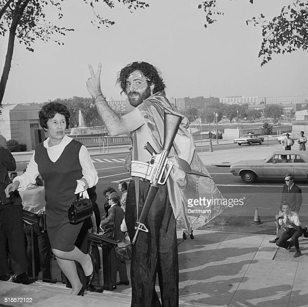 Yippie leader Jerry Rubin carrying a toy machine gun waves a peace sign from the steps of the Cannon House Office building where he attends the House...