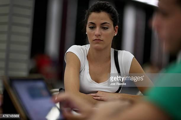 Yislaine Diaz sits with Amaury Garcia an insurance agent from Sunshine Life and Health Advisors as she purchases an individual health insurance...