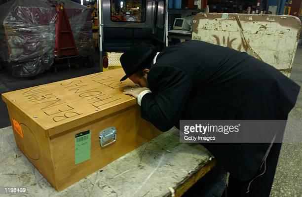 Yisrael Hochstein kisses the casket of Benjamin Blotstein at Israel's Ben Gurion Airport August 1 2002 near Tel Aviv Israel Palestinians seeking...