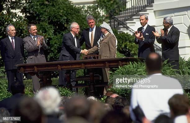 Yitzak Rabin of Israel and Yassir Arafat shake hands after signing the peace accord between Israel and the Palestine Liberation Organization at the...