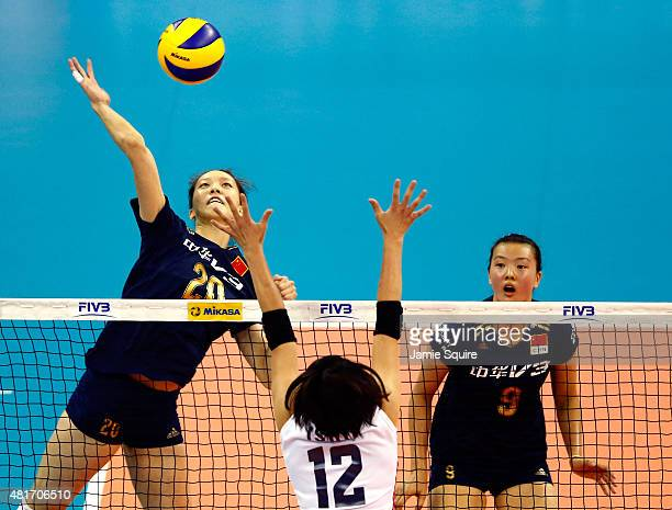 Yixin Zheng of China spikes the ball against Yuki Ishii of Japan as Changning Zhang watches during the final round match on day 2 of the FIVB...