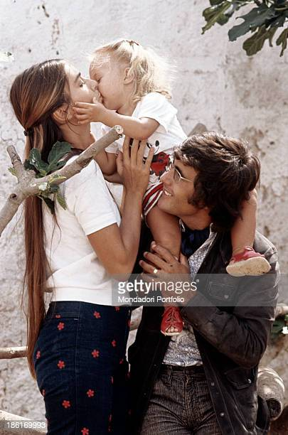 Ylenia Carrisi sitting on the shoulders of her father Italian singersongwriter Al Bano kissing her mother Americanborn Italian singer and actress...