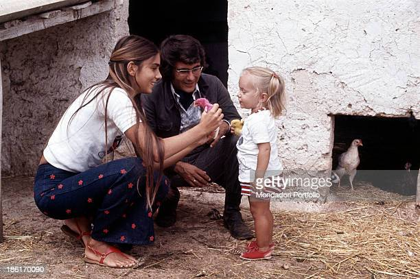 Ylenia Carrisi watching a chick held by her mother Americanborn Italian singer and actress Romina Power beside her father Italian singersongwriter Al...