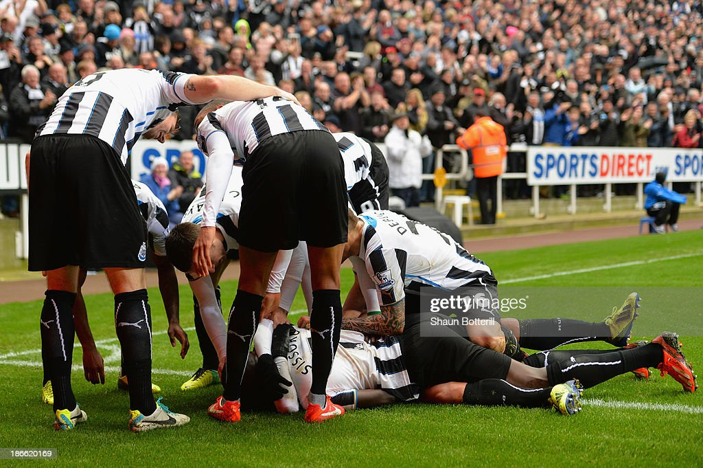 Yoan Gouffran of Newcastle United is mobbed by his team mates after scoring the first goal during the Barclays Premier League match between Newcastle United and Chelsea at St James' Park on November 2, 2013 in Newcastle upon Tyne, England.