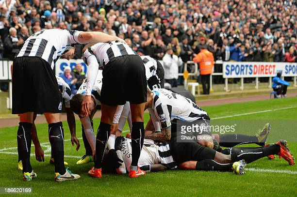 Yoan Gouffran of Newcastle United is mobbed by his team mates after scoring the first goal during the Barclays Premier League match between Newcastle...