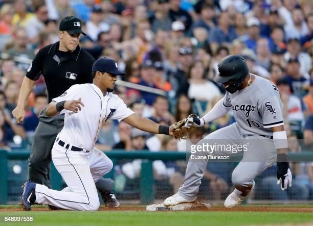 Yoan Moncada of the Chicago White Sox beats the tag from third baseman Jeimer Candelario of the Detroit Tigers to advance from first base on a single...