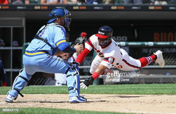 Yoan Moncada of the Chicago White Sox dives in to score a run as Manny Pina of the Milwaukee Brewers awaits the throw in the 5th inning at Guaranteed...