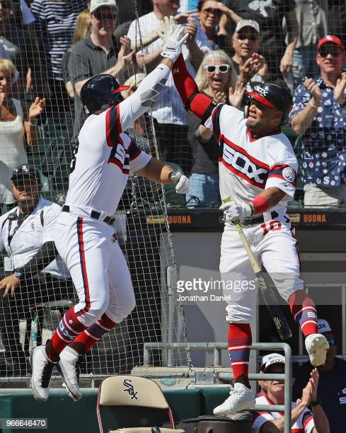 Yoan Moncada of the Chicago White Sox leaps to highfive teammate Daniel Palka after Palka hit a two run home run in the 6th inning against the...