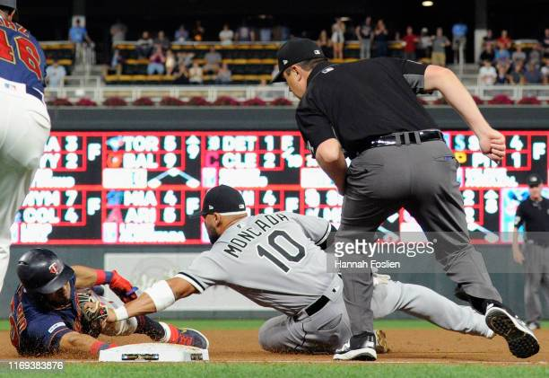 Yoan Moncada of the Chicago White Sox tags out Eddie Rosario of the Minnesota Twins trying to reach third base as umpire Lance Barrett looks on...