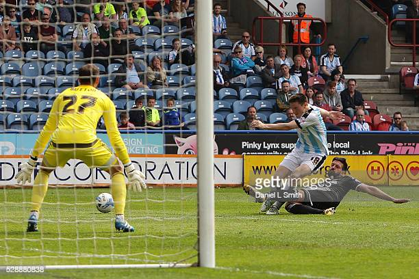 Yoann Barbet of Brentford FC deflects a shot at goal from Joe Lolley of Huddersfield Town FC during the Sky Bet Championship match between...