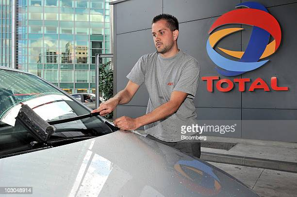 Yoann Bertrand cleans the windshield of his car at a Total SA gas station in Paris France on Thursday July 22 2010 The company Europe's biggest oil...