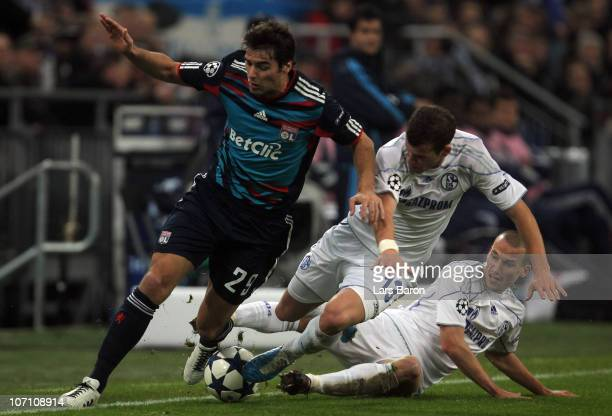Yoann Gourcuff of Lyonnais is challenged by Lukas Schmitz and Peer Kluge of Schalke during the UEFA Champions League group B match between FC Schalke...