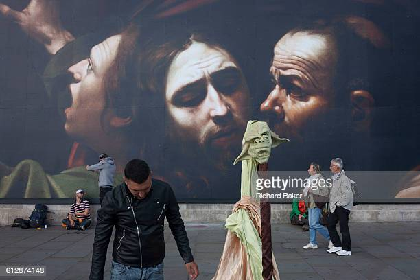 A Yoda costume head and other passersby in front the faces from The Taking of Christ c1602 the painting of the arrest of Jesus by Italian Baroque...