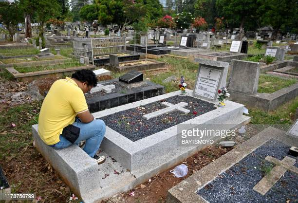 Yoda prays for his best friend who died in the Lion Air plane crash in 2018 at a cemetery in Jakarta October 29 2019 Grieving relatives tossed...