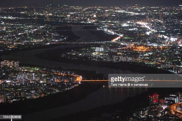 Yodo River in Osaka and Moriguchi cities in Osaka prefecture in Japan night time aerial view from airplane