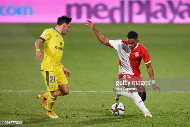 Yoel Barcenas of Girona FC runs with the ball under pressure from Isaac 'Iza' Carcelen of Cadiz CF during the Copa del Rey round of 32 match between...