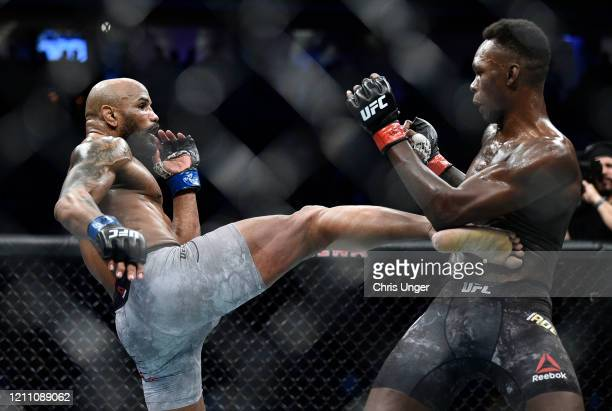 Yoel Romero of Cuba kicks Israel Adesanya of Nigeria in their UFC middleweight championship fight during the UFC 248 event at TMobile Arena on March...