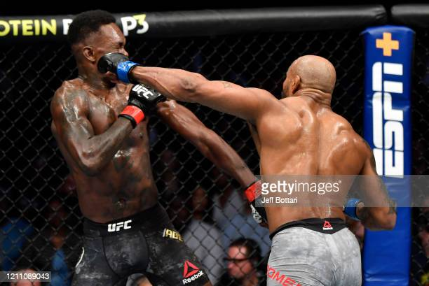 Yoel Romero of Cuba punches Israel Adesanya of Nigeria in their UFC middleweight championship fight during the UFC 248 event at TMobile Arena on...
